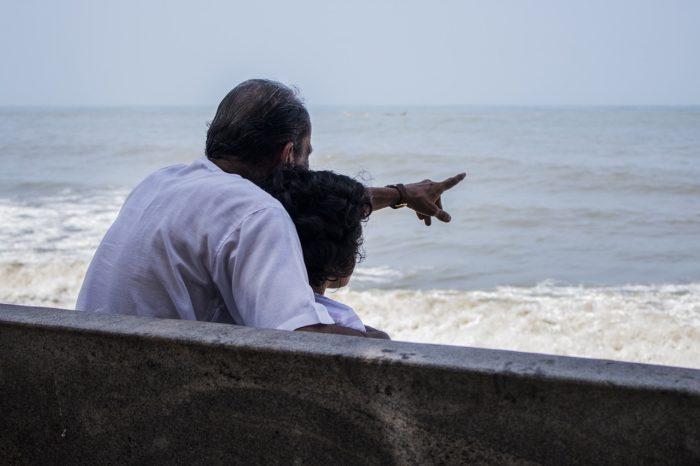 海岸で寄り添うシニアと子ども