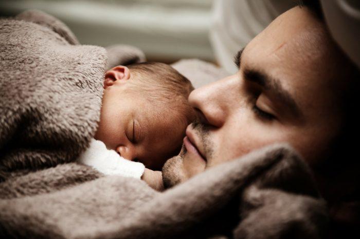ぐっすり眠る赤ちゃんと父親