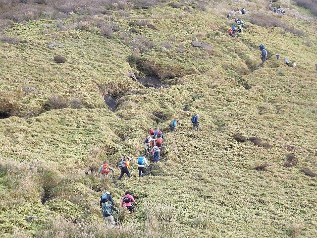 スガモリ越から三俣山西峰をめざす登山者