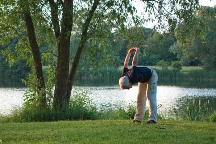 芝生の上でストレッチをするシニア男性